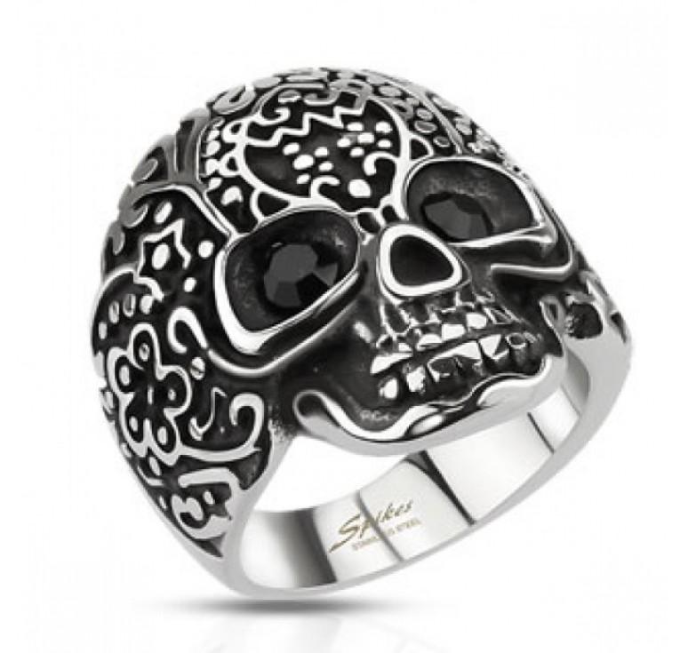Мужское кольцо из стали в виде черепа с узорами. В глазницах камни черные фианиты